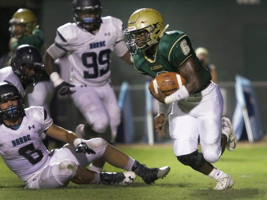 Acadiana running back Regrick Francis looks for a hole in the Barbe defense at Bill Dotson Stadium on Friday night.