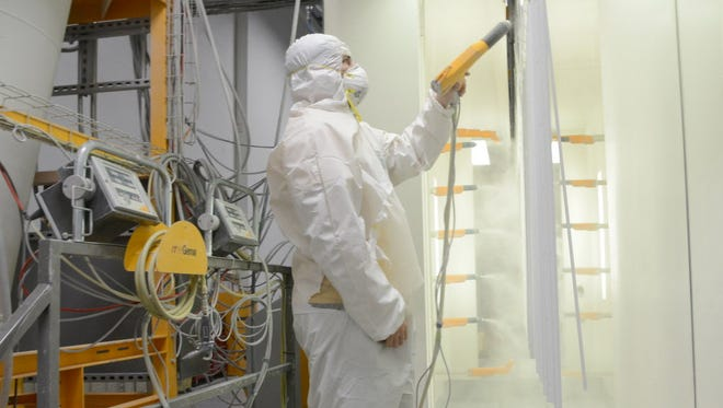 Israel Rojel wears protective clothing as he works on the powder coat paint line at Kenall Manufacturing in April. The company makes a variety of LED lighting products at its facility at 10200 55th St. in Kenosha.