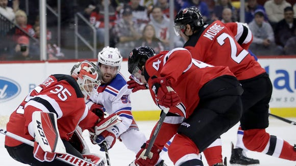 New Jersey Devils goalie Cory Schneider (35) and teammates Sami Vatanen (45), of Finland, and John Moore (2) defend against New York Rangers center David Desharnais (51) during the first period of an NHL hockey game Thursday, Dec. 21, 2017, in Newark, N.J. The Devils were unable to control the puck as Rangers' Jimmy Vesey, not pictured, scored a goal on the play.