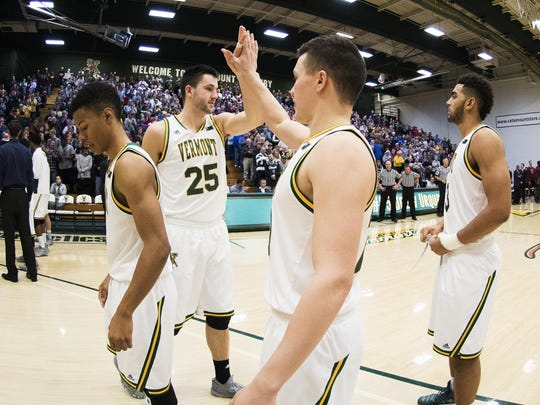 Vermont's Ernie Duncan (20) high-fives Drew Urquhart (25) during the men's basketball game between the Harvard Crimson and the Vermont Catamounts at Patrick Gym on Monday night.