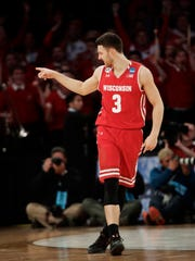 Wisconsin guard Zak Showalter (3) points to Packers quarterback Aaron Rodgers in the stands after hitting a 3-point shot to tie the game against Florida late in the second half of an East Regional semifinal game of the NCAA men's college basketball tournament, Saturday, March 25, 2017, in New York. (AP Photo/Frank Franklin II)