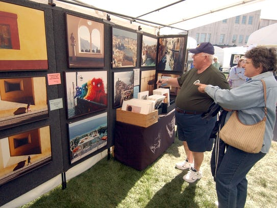 Customers peruse paintings at the Festival of Arts