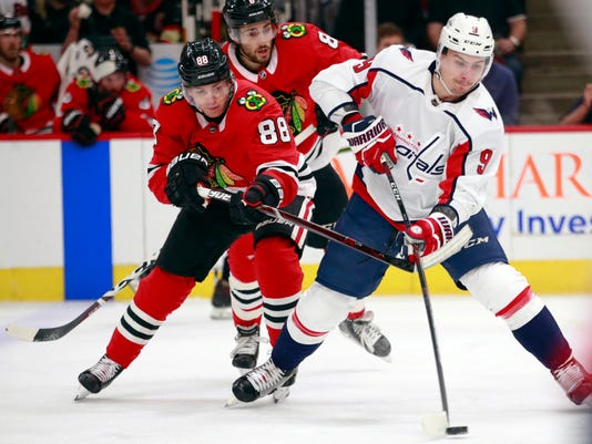 Chicago Blackhawks right wing Patrick Kane (88) battles Washington Capitals defenseman Dmitry Orlov (9) for the puck during the first period of an NHL hockey game Saturday, Feb. 17, 2018, in Chicago. (AP Photo/Jeff Haynes)