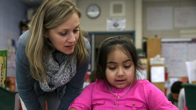Michelle Weisgerber-Westphal, a teacher at Banta Elementary School, helps Natalia Avella Calzado with an independent reading assignment .