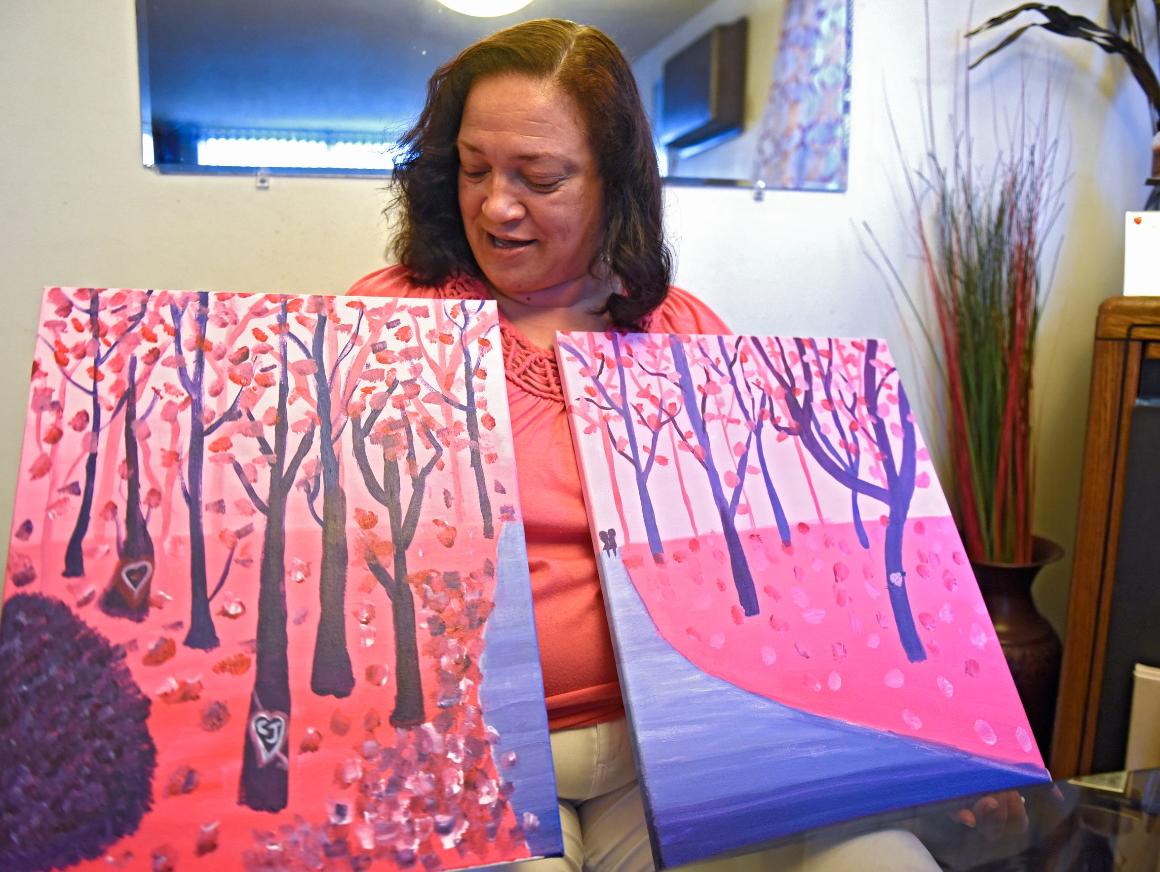 Joy Friedman holds paintings she created with her daughter.