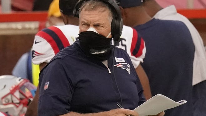 Patriots head coach Bill Belichick wears two masks as he watches from the sideline during Monday's game.