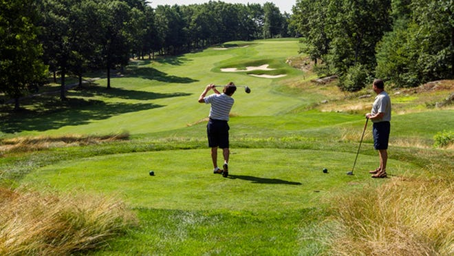 Players drive off the 11th tee at Shaker Hills Country Club in Harvard.