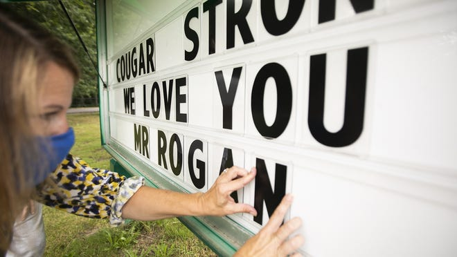Brockton Public Schools Downey School Principal Colleen Proudler finishes the John F. Kennedy Elementary School sign on Ash Street in loving memory of the late Principal Brian Rogan on Monday, July 13, 2020.