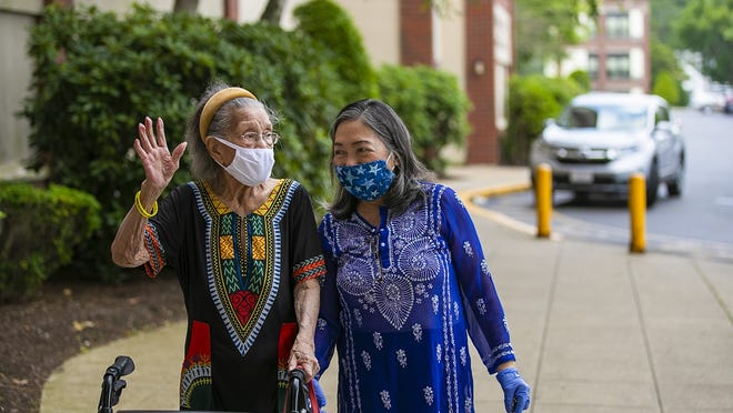 Coronavirus survivor Luisa Antonio, 92, waves to a friend outside the Douglas House as he daughter Alicia Layne, right, helps her inside on Thursday, July 9, 2020. Antonio spent two weeks at Brockton Signature Healthcare Hospital and an additional two months at the Brockton Health Center on Beaumont Avenue fighting COVID-19.