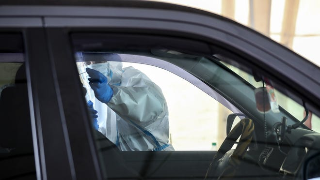 In a May 4, 2020, file photo, Brockton Neighborhood Health Center and Signature Healthcare staff test essential workers in their vehicles for COVID-19 using a nasal swab in the tents at Brockton High School.