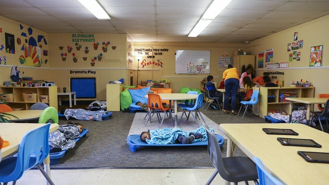FILE - In this Wednesday, March 25, 2020, file photo, toward the beginning of the coronavirus pandemic, children nap or play, depending on their age, at Agape Child Care and Family Life Center in Brockton. Only three of the seven classrooms in the day care were being used during operations as an emergency day care, with a limited number of children per room.
