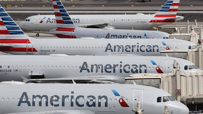 FILE - In this March 25, 2020, file photo, American Airlines jets sit idly at their gates as a jet arrives at Sky Harbor International Airport in Phoenix.