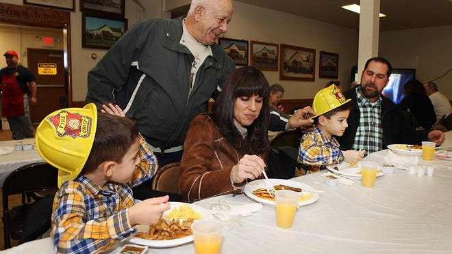 Vineland Fire Company 5 Chief Donald Fiocchi Sr. gives fire hats to Gino Fiocchi (left), 5, and his brother T.J. Fiocchi, 8, who were eating breakfast with their parents, Gina and Todd Fiocchi of North Vineland.