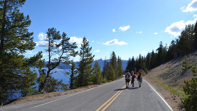 People walk along Rim Drive at Crater Lake on a weekend when half of the road was closed to motorized vehicles.