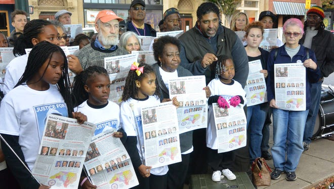 The Rev. William Barber II speaks at an event on Patton Avenue downtown on Wednesday to encourage voter turnout. Those around him are holding NAACP voter guides.