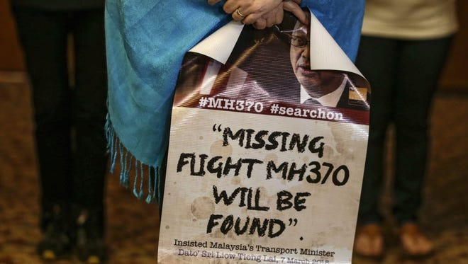 Jacquita Gomes, widow of Patrick Gomes, holds a banner with another next of kin of Malaysia Airlines flight MH370 passenger during a special press conference on July 22 in Kuala Lumpur.