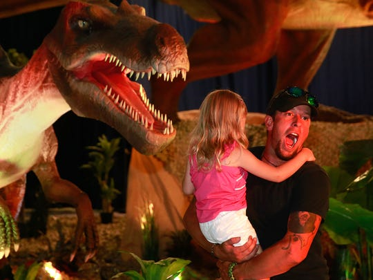Evan Mustill and Serenity Wiggins, 3, get their picture taken with a Tyrannosaurus Rex during the Discover the Dinosaurs Unleashed exhibit on Saturday at the McGee Park Convention Center.