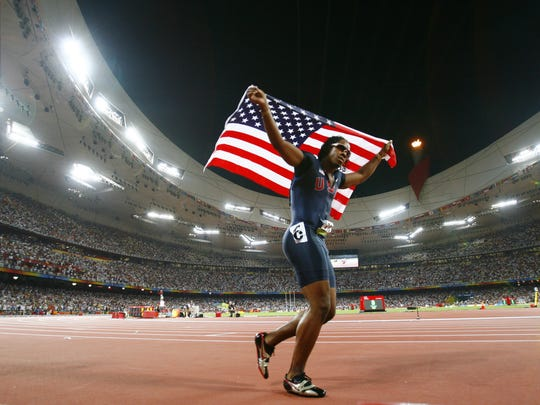 United States' Walter Dix celebrates with the U.S. flag after capturing a bronze medal in the men's 100-meter dash at the 2008 Olympics in Beijing.