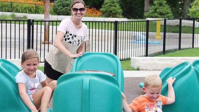 Amy Levin gives her children, Eisley, left, and Luke a spin at the playground at the splash pad on Water Street Tuesday. The playground portion is open and Parks and Recreation Director Taylor Baxter is hoping to have the splash pad open by this weekend.