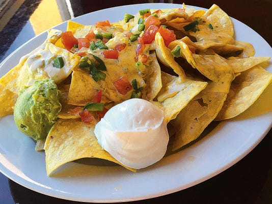 Sunset Nachos (7.95) is made with house made tortilla chips and topped with pico de gallo, jalapeños and nacho cheese sauce mixed with Sunset Grill's house salsa.