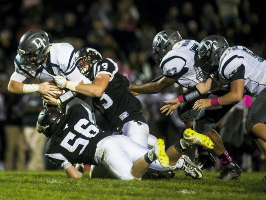 Dallastown ball carrier Michael Hernandez gets dragged down by South Western defenders Corbin Byers and Evan Raubenstine (56) on Friday.