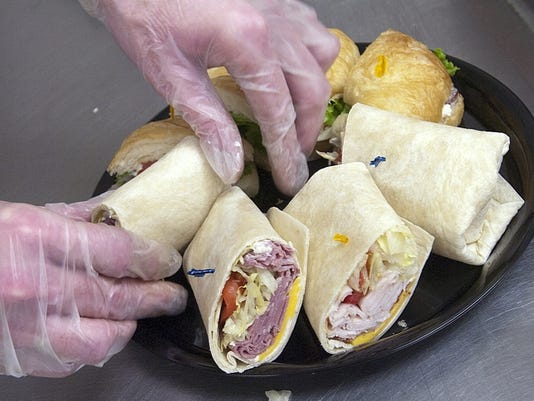 Alan Paullet, owner of Paullet's bakery, puts the finishing touches on some wraps.