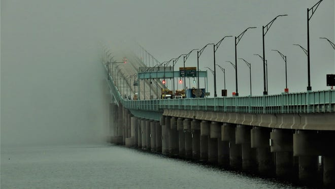 The Newport Pell Bridge is partially shrouded in fog.