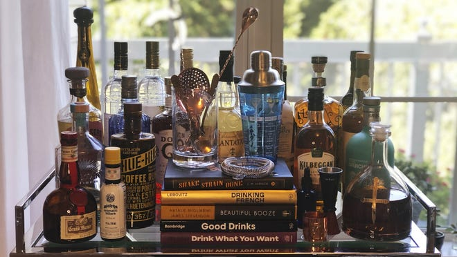 A collection of spirits and cocktail recipe books are displayed at a home in Alexandria, Virginia. Since the pandemic hit the United States, a lot of social drinking has moved back home.
