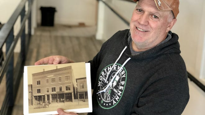 Penny Pinchers Brewing Co. co-founder Jody Barton with an old picture of the storefront where he is opening the brewery. The building has been around for many years - at one time it was home to a consignment shop, bakery and pharmacy.