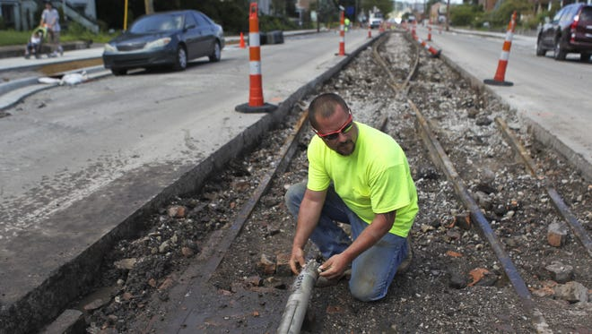 Old trolley tracks can bee seen as Troy Collins of Hummel Electric of Evansville works on a coring bit that is digging a conduit line for up to 67 lights that will be installed along a median on Main Street in New Albany as part of a downtown improvement project. The trolley tracks are being taken out due to structural concerns. The tracks will likely be used for scrap metal. Medians will be installed to slow traffic as well as house plants and trees that will beautify the area once completed.