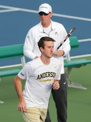 Jeffrey Dayton, below, runs by coach Joey Eskridge during practice at the Anderson University Sports Complex tennis courts.