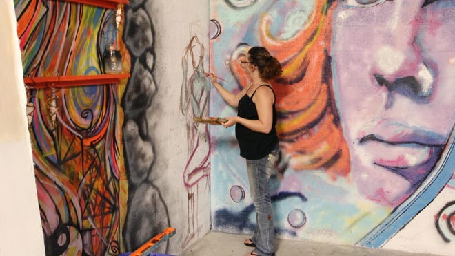 Artist Lesley Morrow works on painting part of the wall at The Epicenter on Wednesday. The Epicenter is a new art center that is open to artists of all disciplines.