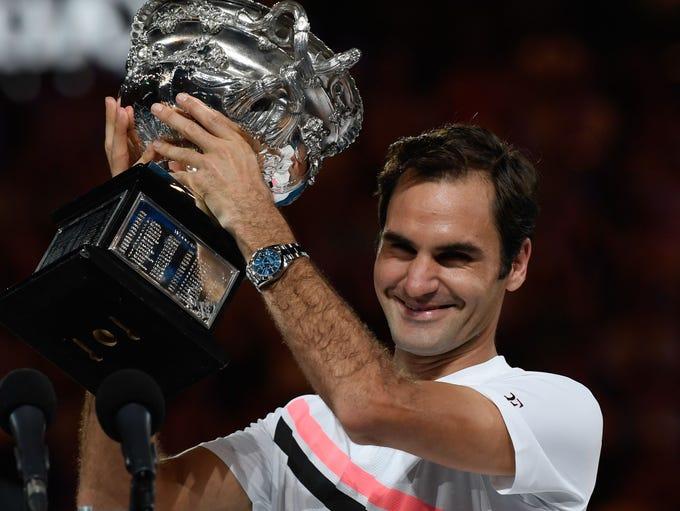 Roger Federer holds the Australian Open trophy, celebrating