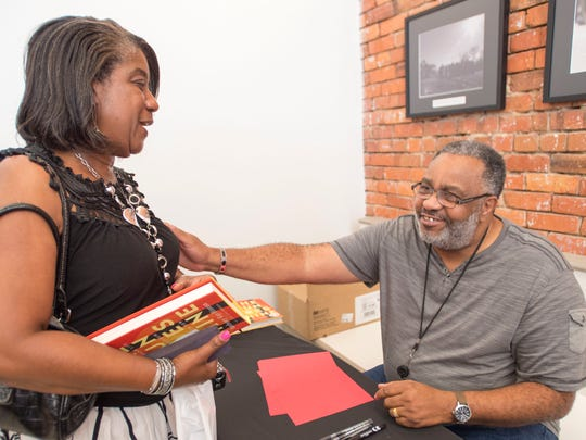 "Anthony Ray Hinton, right, the former Jefferson County inmate who was exonerated after spending 30 years on Alabama's death row for a crime he did not commit, signs a copy of his new book ""The Sun Does Shine: How I Found Life and Freedom on Death Row"" for Audrey Darby of Montgomery Wednesday, June 13, 2018, at the Equal Justice Initiative's bookstore in Montgomery, Ala."