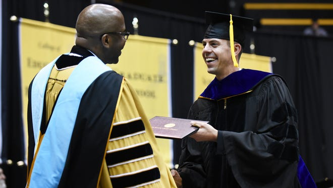 University of Southern Mississippi graduate David Krzeminski receives his diploma during the graduation ceremony Friday at Reed Green Coliseum