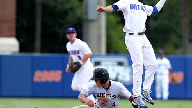 Florida's Dalton Guthries, right, catches a throw from catcher Mike Rivera as Wake Forest runner Stuart Fairchild (4) safely steals second base during the first game of a super regional in the NCAA college baseball championship held at McKethan Stadium in Gainesville, Fla., Saturday, June 10, 2017. (Brad McClenny/The Gainesville Sun via AP)