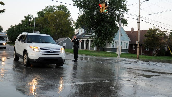 EPD Officer directs traffic through the intersection of  Weinbach and Bellemeade after a water main break in Evansville on Tuesday August 19,2017.