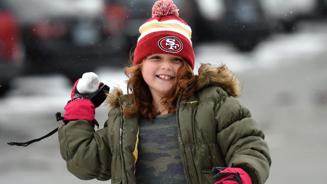 A file photo showing Sophia Klesow, 8, of Concord, Calif., playing catch with a snowball next to the skating rink in downtown Reno. Local forecasters expect rain, snow and high winds as a winter storm hits the Reno-Tahoe area on Wednesday through Thursday.