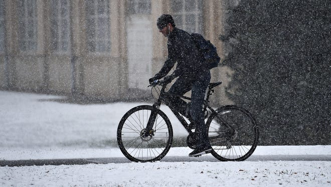 A biker travels south on College Avenue during the first seasonal snow on Thursday, November 17, 2016.
