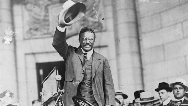 Theodore Roosevelt waves to the crowd.