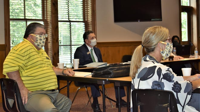 Bryan County schools Superintendent Paul Brooksher, center, and board members Derrick Smith, left, and Marianne Smith listen to a presentation about e-learning Thursday night at a school board workshop.