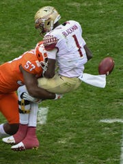 Clemson linebacker Tre Lamar (57) hits and forces a fumble by Florida State quarterback James Blackman (1) during the first quarter in Memorial Stadium at Clemson on Saturday.