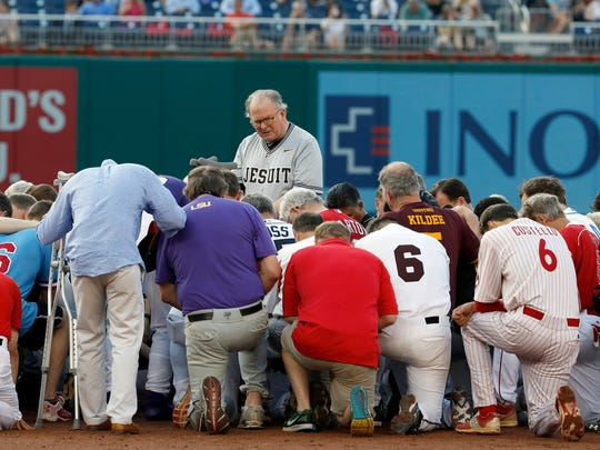 The Rev. Patrick J. Conroy, chaplain of the U.S. House of Representatives, prays as both teams kneel before the Congressional baseball game June 15, 2017, in Washington, D.C. The annual GOP-Democrats baseball game raises money for charity.
