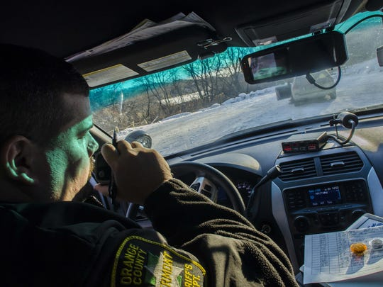 Orange County Sheriff's Deputy Jean Miguel Bariteau speaks with his dispatcher after stopping a driver for using a hand-held cell phone in Barre Town on Thursday, January 14, 2016.
