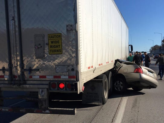 A car crumpled underneath a semi-truck on eastbound