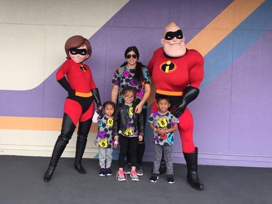 """Brianna Benito and her kids pose with characters from Pixar's """"The Incredibles"""" on vacation at Tokyo Disneyland."""