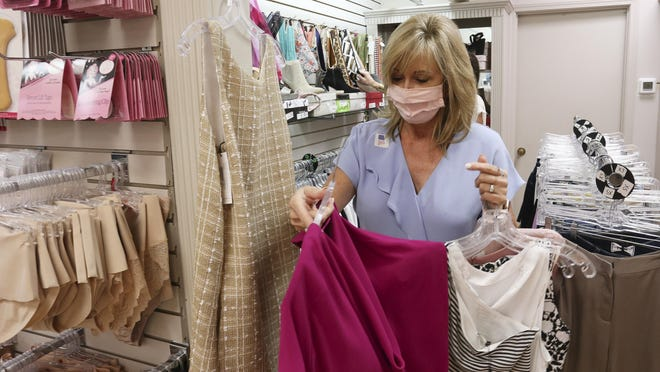 Effie's Inc. owner Terry Davis brings clothing to a fitting room as she helps a customer in Tuscaloosa Tuesday, July 14, 2020. Davis and other retailers are preparing for the sales tax holiday this weekend on back-to-school supplies.