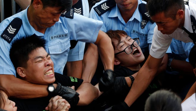 Protesters are taken away by police officers after hundreds staged peaceful sit-ins overnight in Hong Kong Wednesday following a huge rally to support democratic reform.