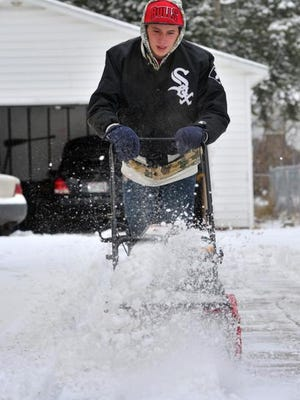Blayze Coseale, of Wausau, plows snow Monday morning at his house.