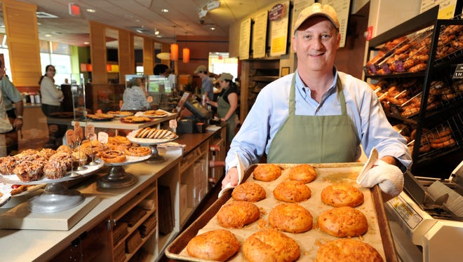 Panera CEO Ron Shaich poses with a tray of Asiago cheese bagels at a Panera Bread cafe in Needham, Mass.